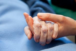 Elderly holding young hand